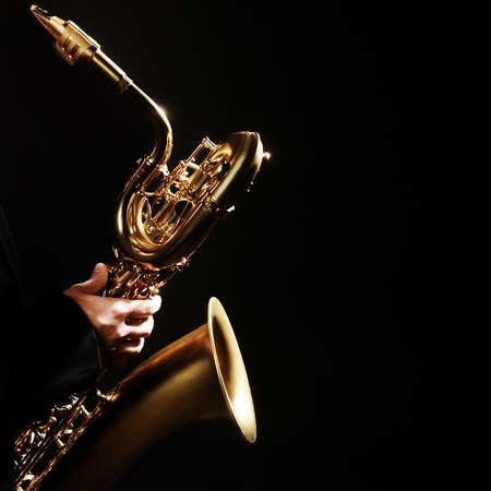 saxofon: Jugador del saxofón del jazz del instrumento de música del saxofón del barítono aislado en negro
