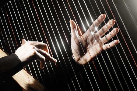 orquesta: Harp cuerdas manos primer. Arpista con instrumento de música clásica