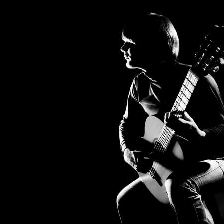 photography: Acoustic guitar player guitarist. Classical guitar concert playing musical instrument in darkness