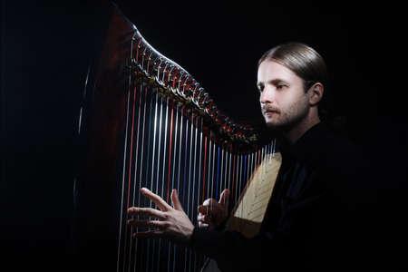 the harp: Jugador de la arpa. Clásica arpista músico que toca el instrumento musical arpa irlandesa