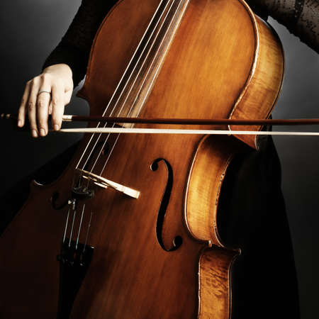 cellist: Cello player cellist playing music instrument hands closeup. Orchestra instruments