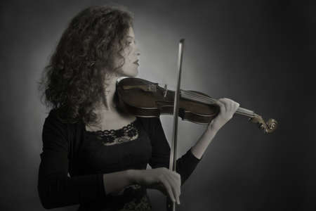 fiddles: Violin player violinist classical musician woman playing violin musical instrument Stock Photo