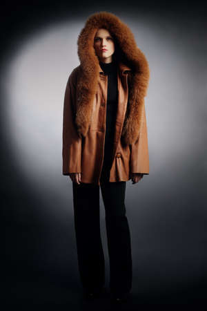 greatcoat: Woman in winter clothes fashion coat. Leather jacket with hood cowl Stock Photo