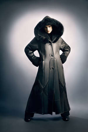 greatcoat: Sheepskin coat winter clothes. Winter fashion woman in long coat with hood cowl