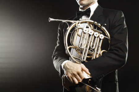 French horn player closeup. Classical musician hornist with horn music instrument