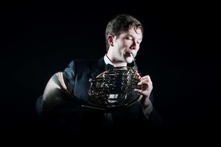 cuernos: El jugador cuerno francés. músico clásico instrumento de reproducción de música aislado en negro