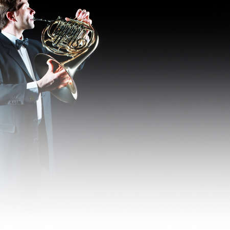 french horn: French horn player. Classical musician hornist playing horn music instrument