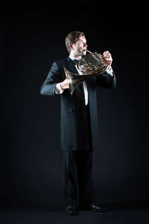 french horn: French horn player with music instrument. Classical musicians playing musical instruments.