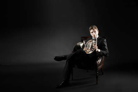 french model: French horn player portrait. Elegant man classical musician with music instrument Stock Photo