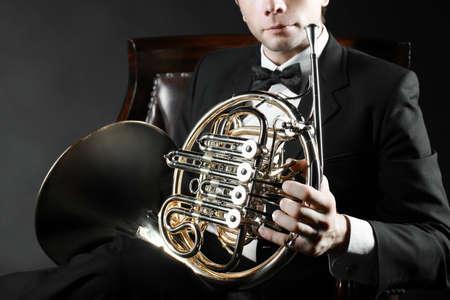 cuernos: El jugador cuerno francés. cuerno de la música del instrumento en las manos de hornist