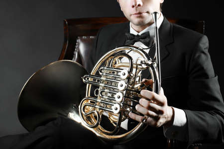 symphonic: French horn player. Music instrument horn in the hands of hornist