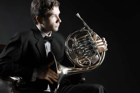 french horn: French horn player. Classical musician hornist with horn music instrument