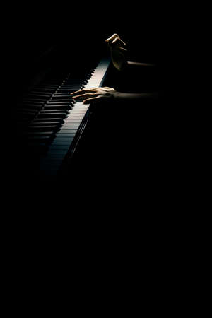 Grand piano player Pianist hands playing piano keyboard isolated on black