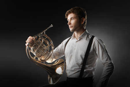 cuernos: El jugador cuerno francés hombre músico clásico que juega el claxon instrumento de música