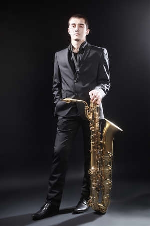 symphonic: Saxophone player musician with jazz music instrument baritone sax. Saxophonist jazz man portrait Stock Photo