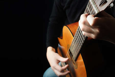 Acoustic guitar guitarist playing classical guitar detail. Musical instruments with musician hands. Banco de Imagens