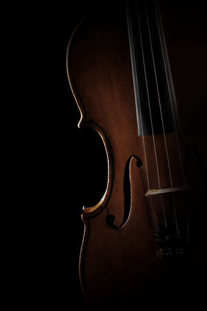 cellos: Violin closeup Musical instruments of orchestra. Silhouette violin isolated on black background close up