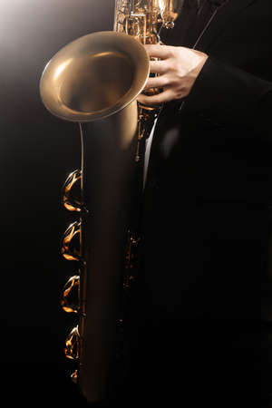 professional flute: Saxophone player Saxophonist playing jazz music instrument sax baritone Jazz musician hands closeup