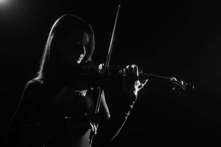 Violin player Violinist playing violin classical music concert in darkness