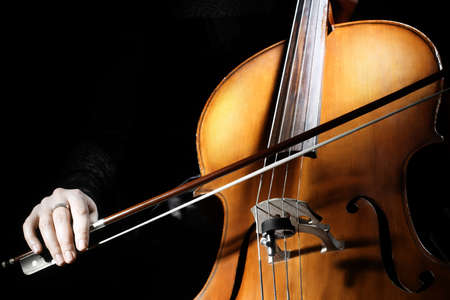 cellos: Cello player Cellist hands playing cello with bow orchestra musical instruments Stock Photo