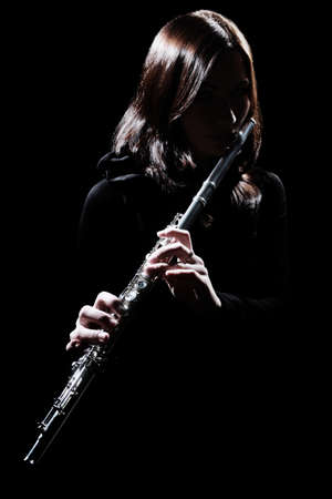 Flute player Flutist playing flute instrument. Classical musician isolated on black Stock Photo