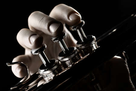 Trumpet player. Trumpeter hands playing brass musical instrument close up