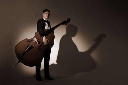 symphonic: Classical musician studio portrait. Double bass player with contrabass Stock Photo
