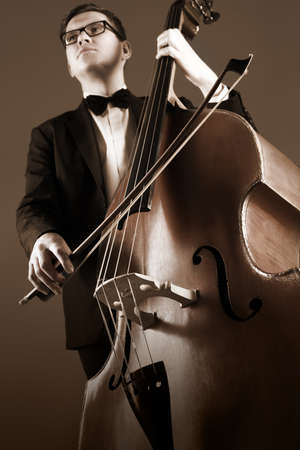 soloist: Double bass player playing contrabass. Classical musician. Focus is on the strings with bow Stock Photo