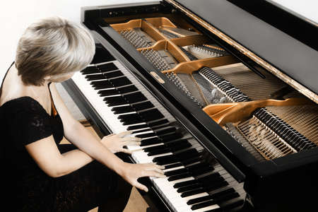 Piano player. Pianist woman playing grand piano