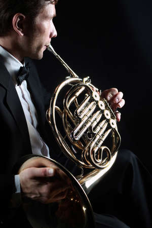 French horn player. Classical musician playing horn instrument