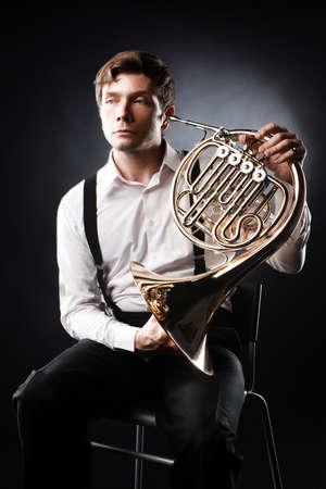 French horn player. Classical musician portrait playing horn instrument Standard-Bild