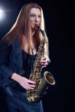Saxophone player. Saxophonist woman playing Sax player jazz musician. Standard-Bild