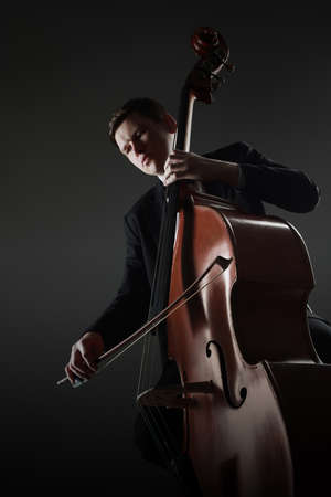 Double bass player contrabass playing with bow. Classical musician