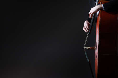 Double bass player. Hands playing contrabass. String musical instrument