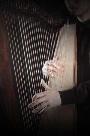 Harp player. Harpist playing Irish harp celtic Hands strings close up