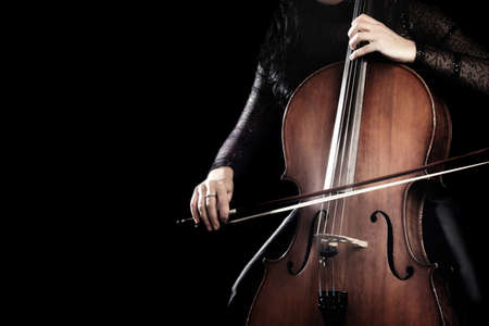 Cello player. Cellist hands playing cello with bow orchestra musical instrument close up
