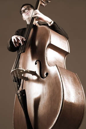 Double bass player contrabass playing. Classical musician jazz bassist. Focus is on the strings