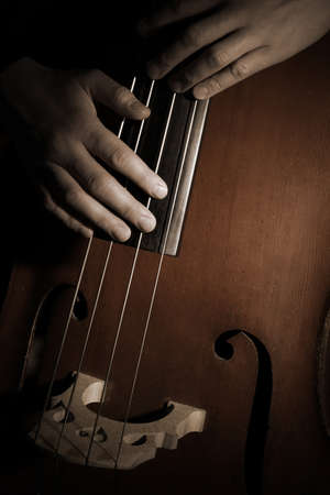Double bass player Hands playing contrabass musical instrument. Strings cello