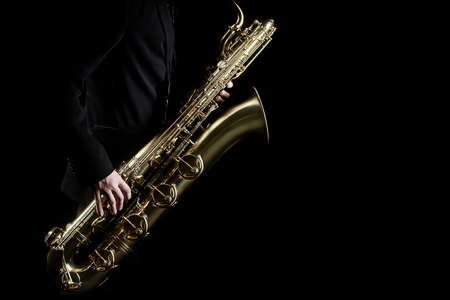Saxophone player jazz music instrument. Sax player saxophonist with baritone saxophone hands close up