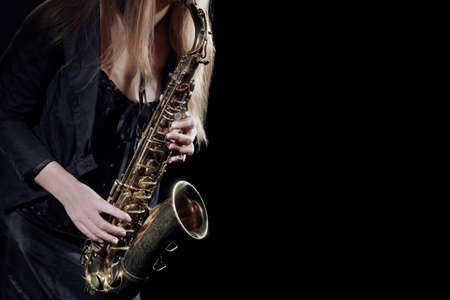 Close-up view of saxophonist playing jazz music with the music instrument.