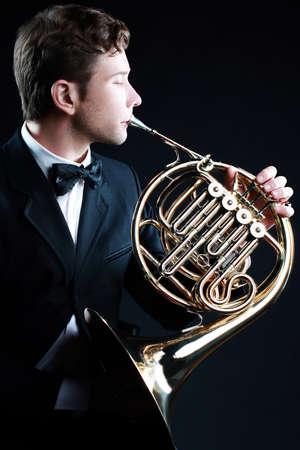 French horn player classical musician. Hornist playing music horn instrument. Standard-Bild