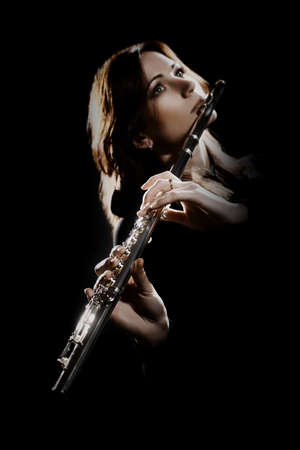 Flute player. Flutist playing flute music instrument. Classical musician woman isolated on black. Focus is on the hands