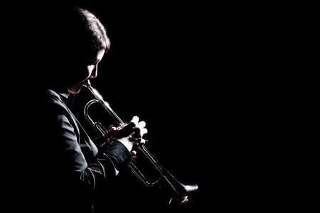 Trumpet player jazz musician playing brass instrument. Jazz trumpeter isolated on black background