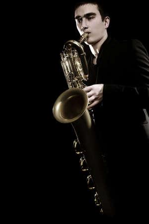 Saxophone player Jazz musician. Saxophonist playing jazz music. Baritone sax player isolated on black closeup