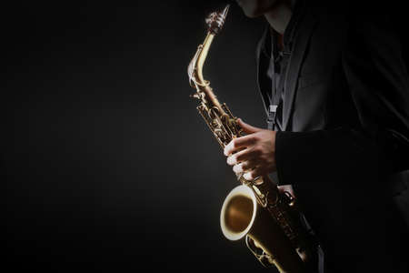 Saxophone player. Saxophonist hands playing saxophone. Alto sax player with classical music instrument closeup 스톡 콘텐츠