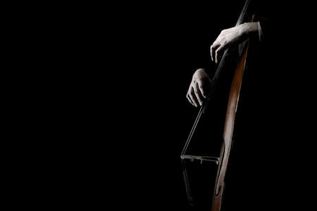 Double bass strungs. Contrabass isolated on black. Hands playing music instrument closeup 写真素材