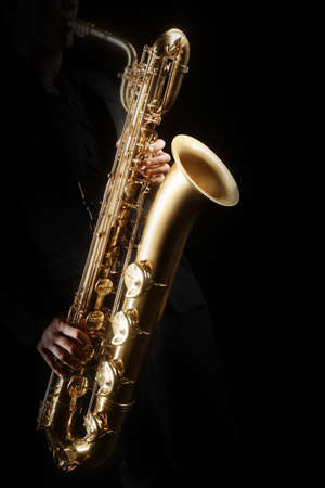 Saxophone player Saxophonist playing jazz music. Baritone sax player isolated on black closeup hands