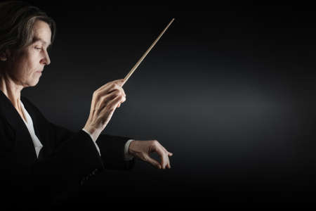 Orchestra conductor music conducting. Woman leader Maestro hands with baton Banco de Imagens