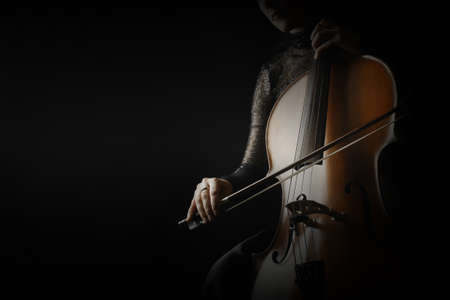 Cello player. Cellist hands playing cello with bow orchestra musical instrument closeup Banco de Imagens