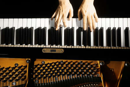 Piano keys closeup. Piano player. Pianist hands playing grand piano Banco de Imagens